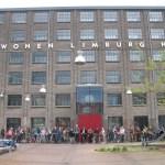 groepsfoto voor het fabrieksgebouw aan de Veeladingsstraat.