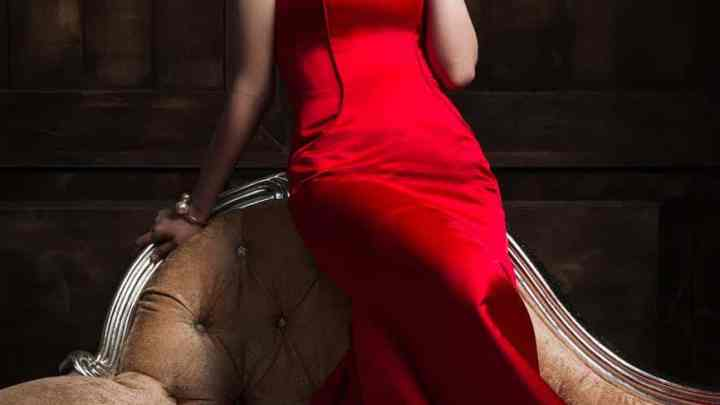 elegant dreamy asian woman in red dress on couch