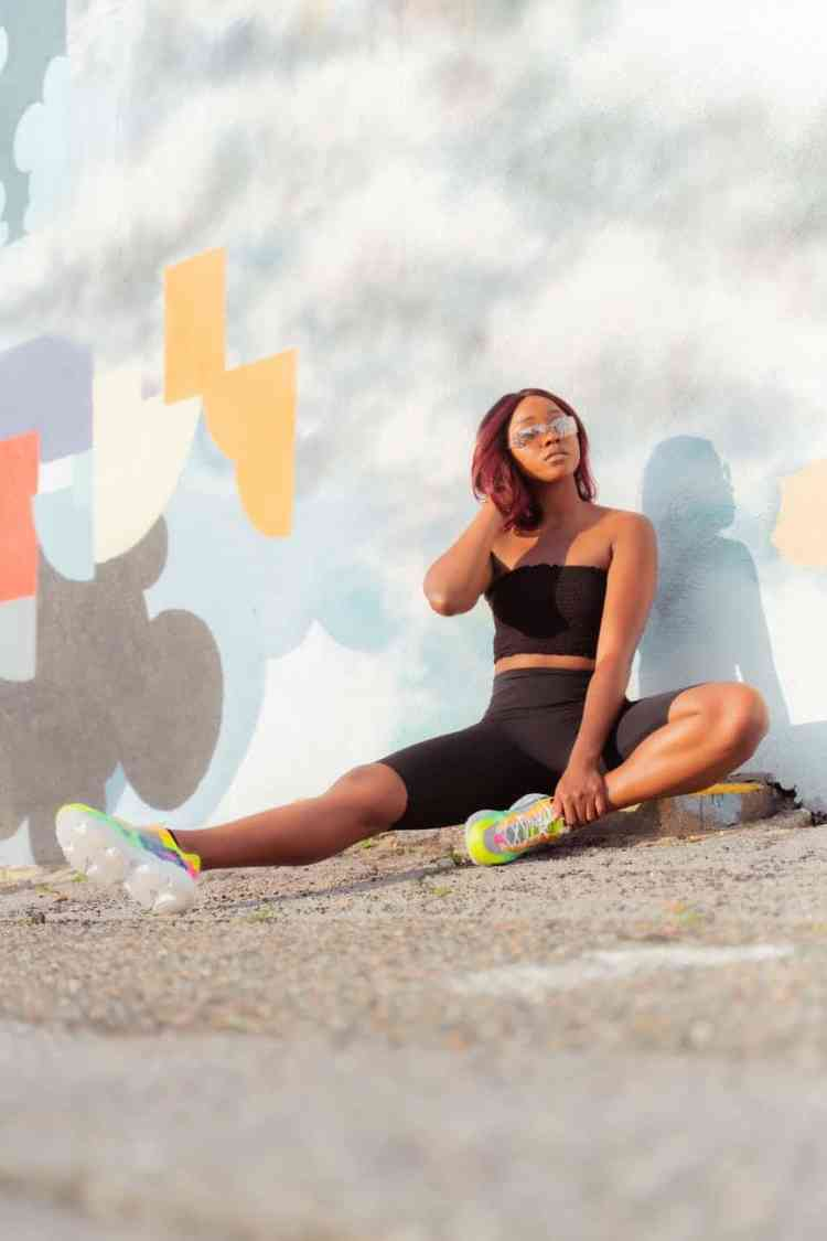 young black woman in sportswear sitting on asphalt near building