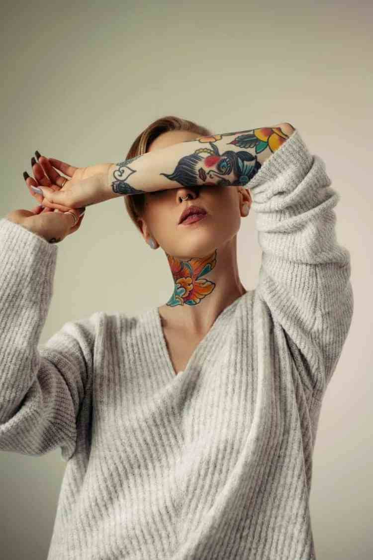 unrecognizable stylish tattooed woman on light background