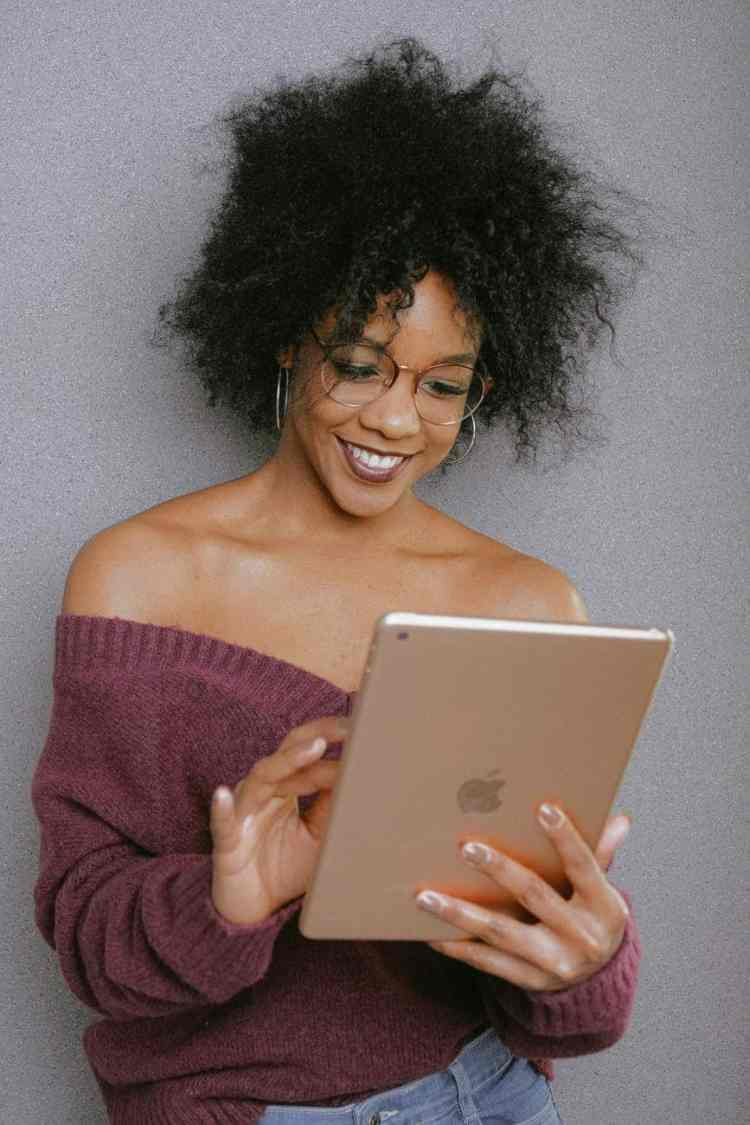 woman in purple off shoulder top holding an ipad
