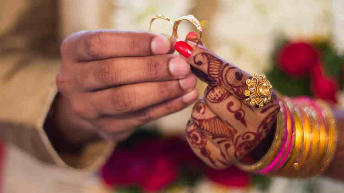 man and woman holding wedding rings