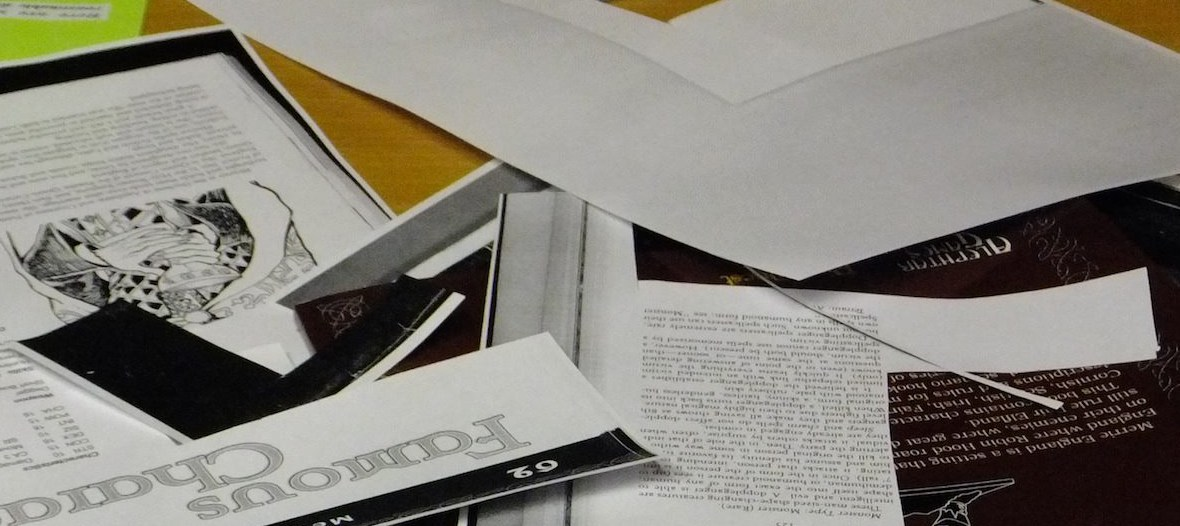 A picture of various roleplaying game pages, scattered on a table, cut up to make zines.