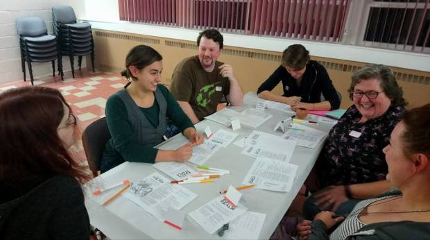 A group of people gathered around a table, smiling, while playing a roleplaying game called Dream Askew.
