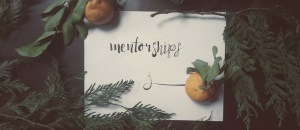 A photograph of a piece of paper with a stylized word written on it: mentorships. The paper is surrounded by cedar branches and mandarin oranges.