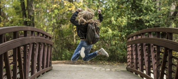 Girl with backpack jumping on a bridge