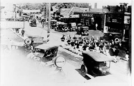Virtue Motors with a parade band marching on Lakeshore Road, ca 1920