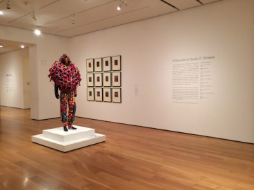 """Exhibition view, with a Nick Cave Soundsuit, 2005, and David Driskell's """"Doorway"""" print series, 2008."""