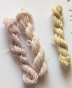 three skeins of wool, pale pink, paler pink and yellow