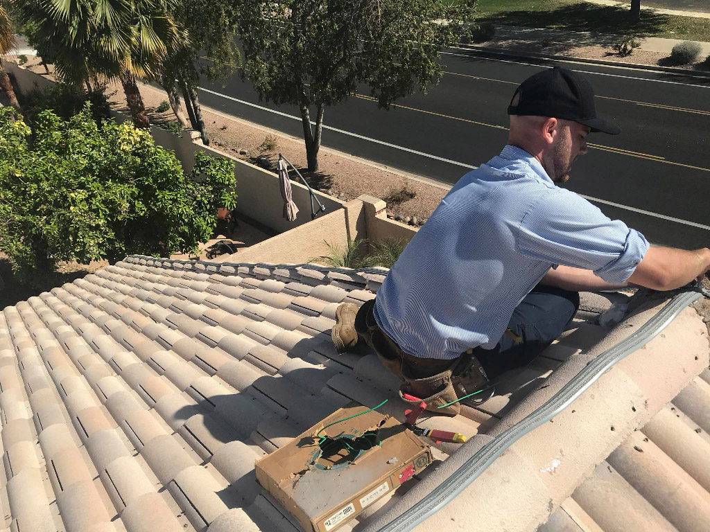 Technician on roof installing bird prevention.