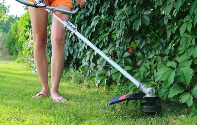 Woman using a weed wacker.