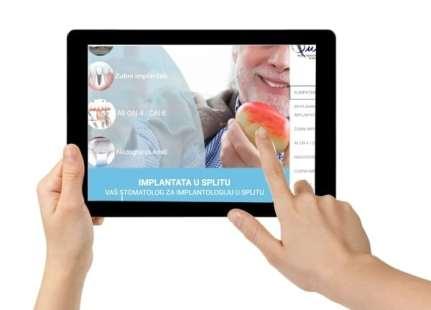 Der Finger zeigt auf dem Tablet auf unsere Implantat-Website