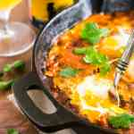 A skillet of beer-lamb shakshuka with a beer and cilantro in the background.