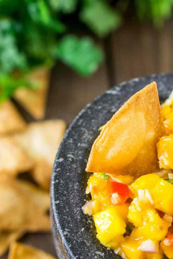 A closeup of a tortilla chip scooping up tropical pico de gallo.