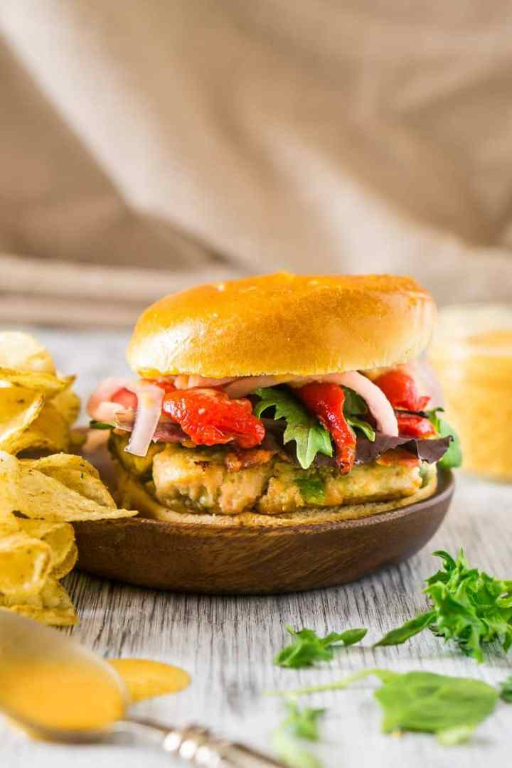 A salmon-avocado burger on a wooden plate with chips.