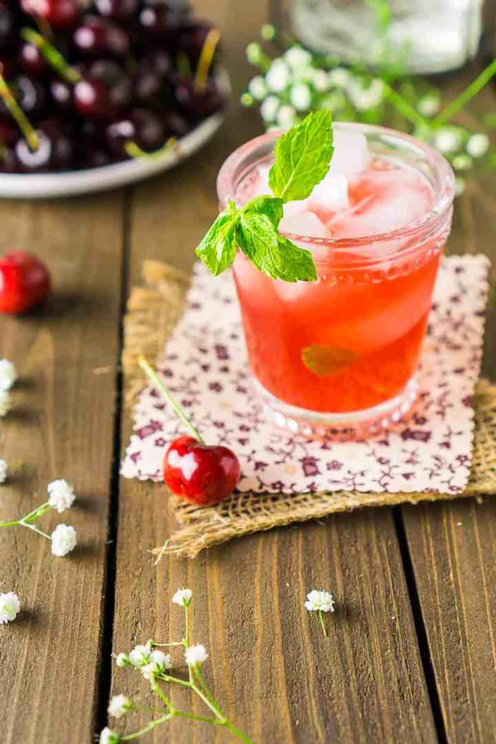 A cherry bourbon smash with a mint sprig garnishing the drink.