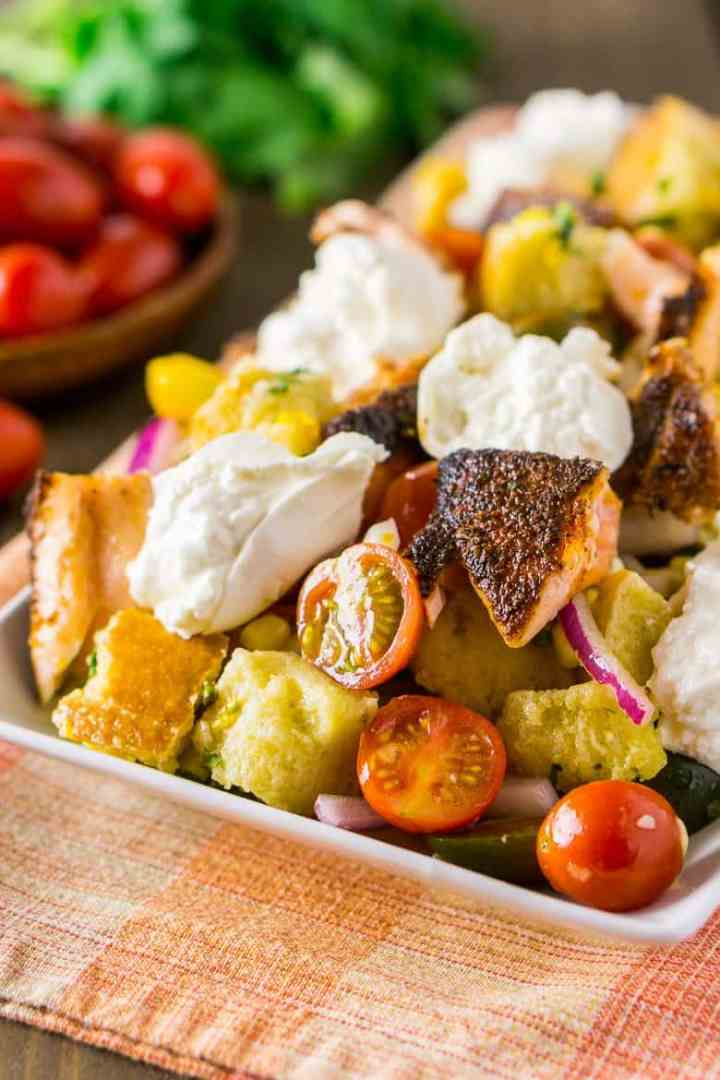 A rectangular plate of burrata-blackened salmon panzanella salad with fresh cherry tomatoes.