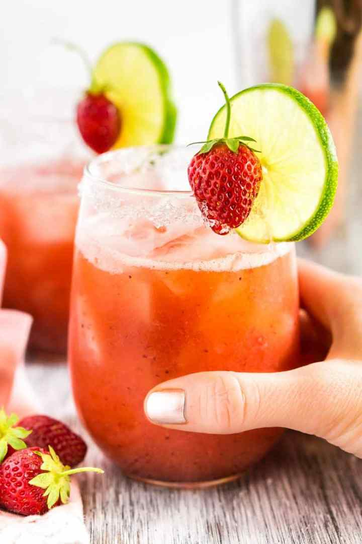 A hand grabbing a roasted strawberry margarita.