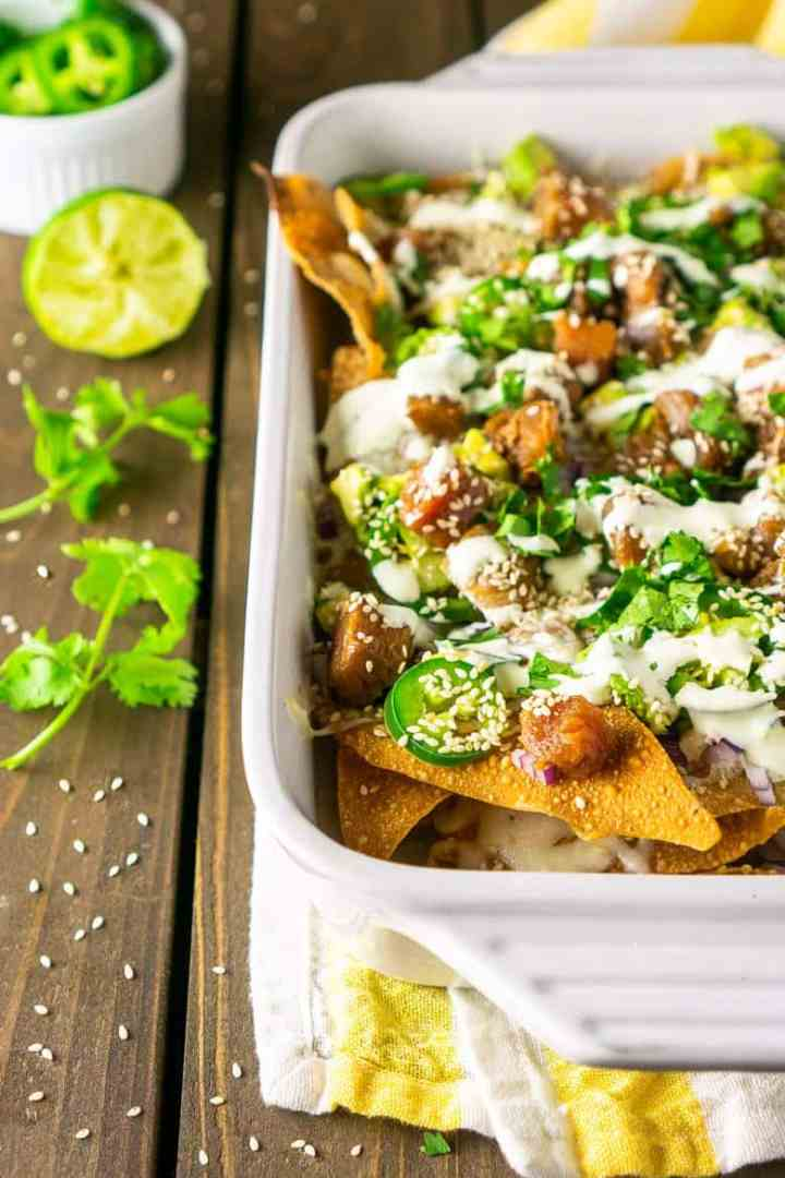 A white baking dish filled with ahi nachos with wasabi Crema with cilantro and lime on the side.
