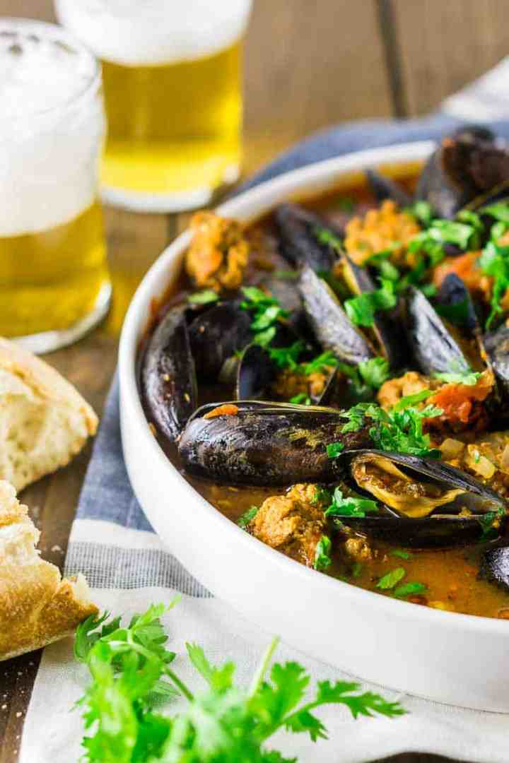 A white bowl of beer mussels with crusty bread on the side of two pilsners.