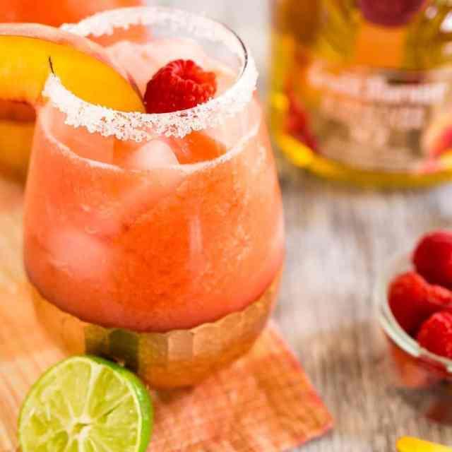 Two raspberry-peach margaritas with fresh fruit.
