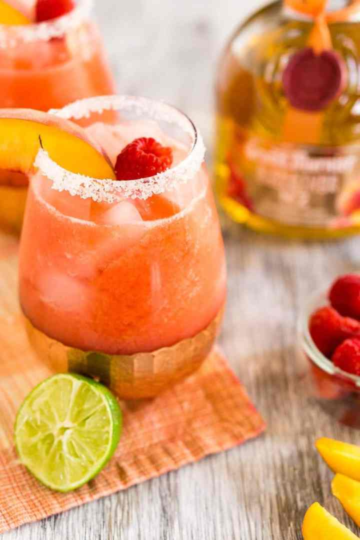 Two raspberry-peach margaritas with fresh fruit.
