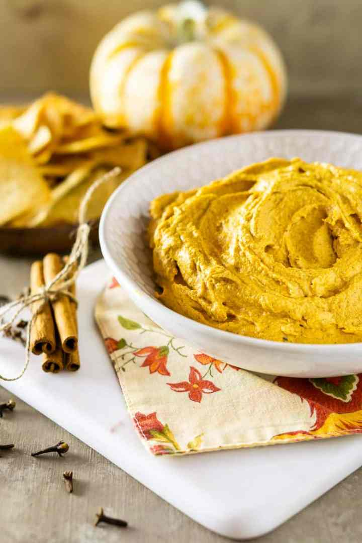 Pumpkin-chipotle hummus on a marble serving tray with pita chips and a pumpkin.