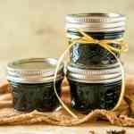 Brown sugar-chai tea simple syrup in mason jars stacked as a pyramid.