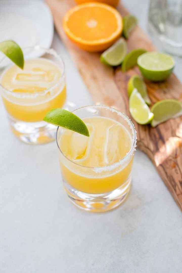 Two skinny margaritas with a wooden board holding limes and oranges.