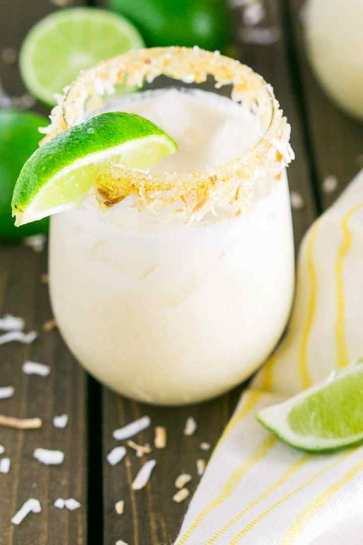 A coconut margarita surround by lime slices and toasted coconut.