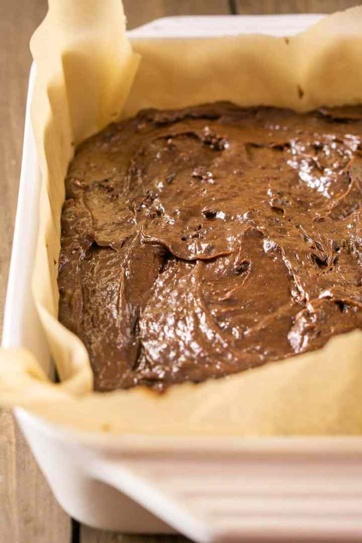 Fudgy stout brownie batter poured into a parchment paper-lined pan.