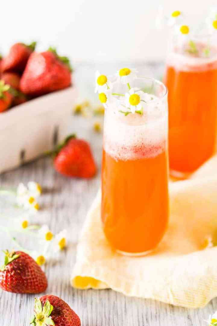 Two roasted strawberry Aperol spritzes with a basket of fresh strawberries.