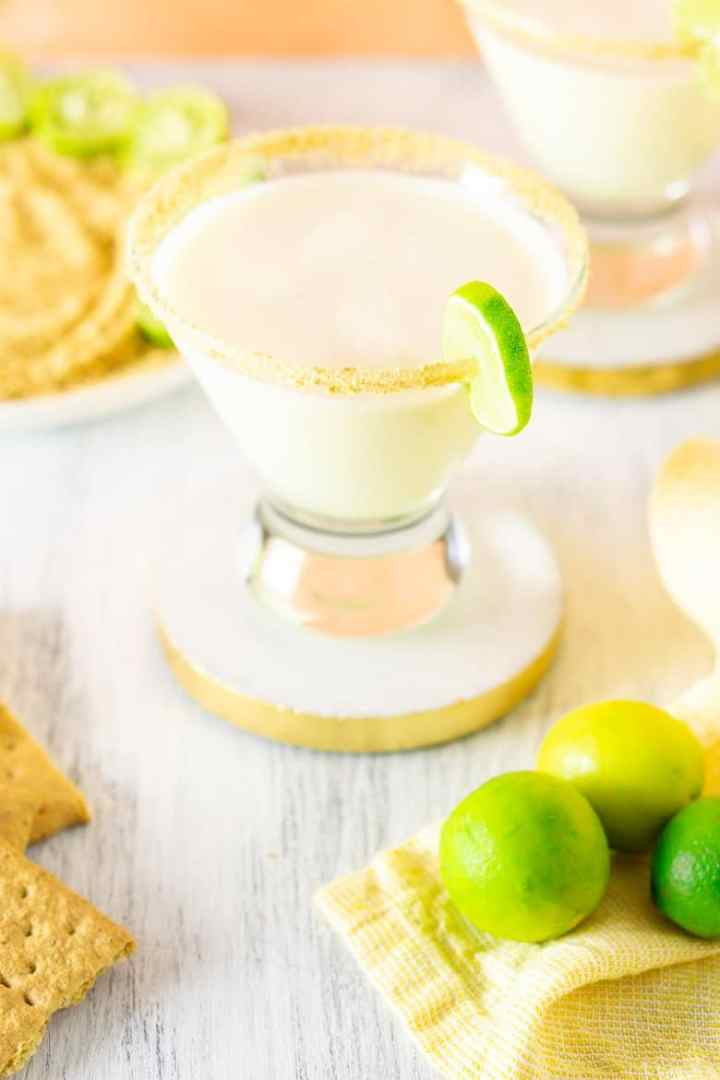 Two sparkling key lime pie martinis with crushed graham crackers and key limes.