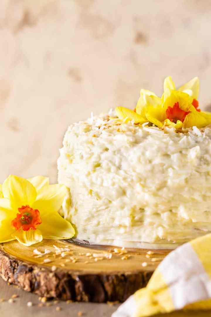 The homemade carrot cake frosted in coconut cream cheese frosting on a wooden cake stand.