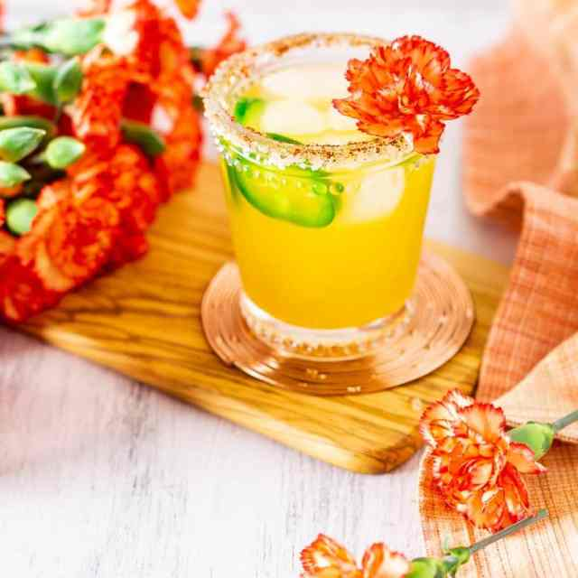 A jalapeno-mango margarita with flowers in the background.