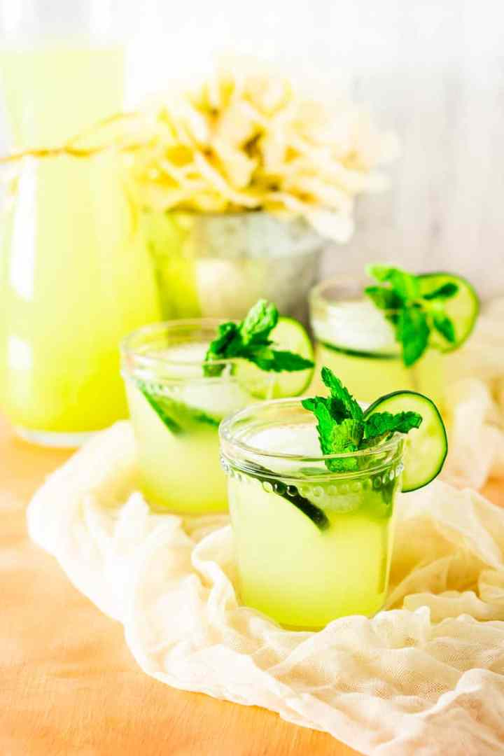 A front view of three glasses of mint-cucumber lemonade with flowers in the background.
