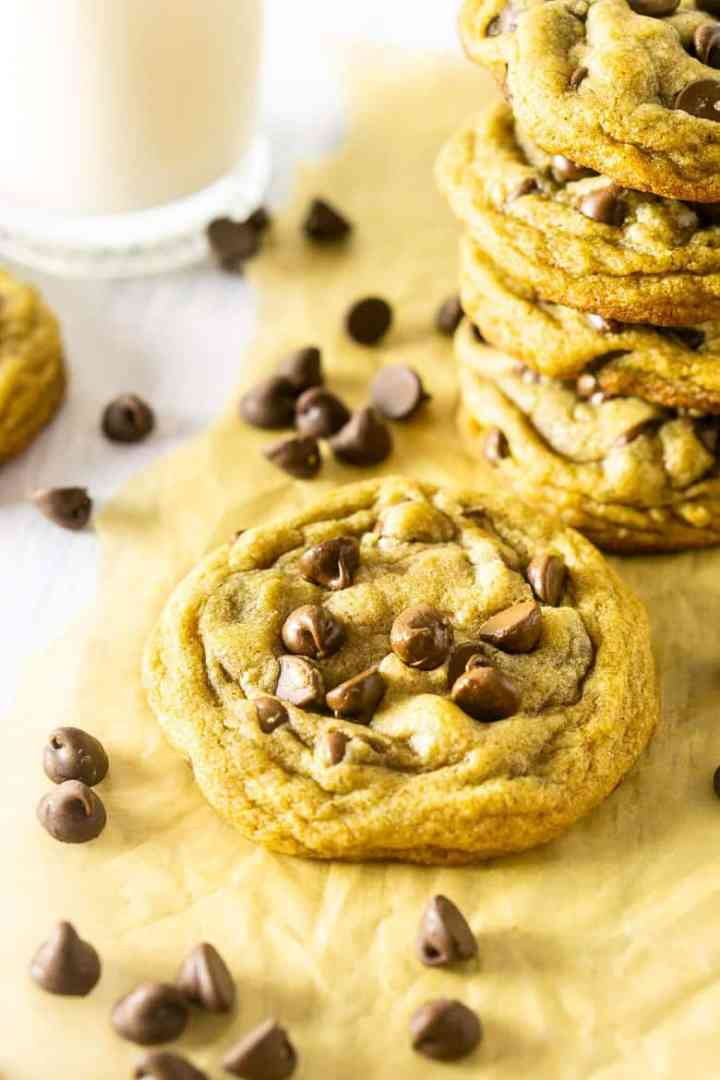 A single brown butter chocolate chip cookie with a stack of cookies in the background.
