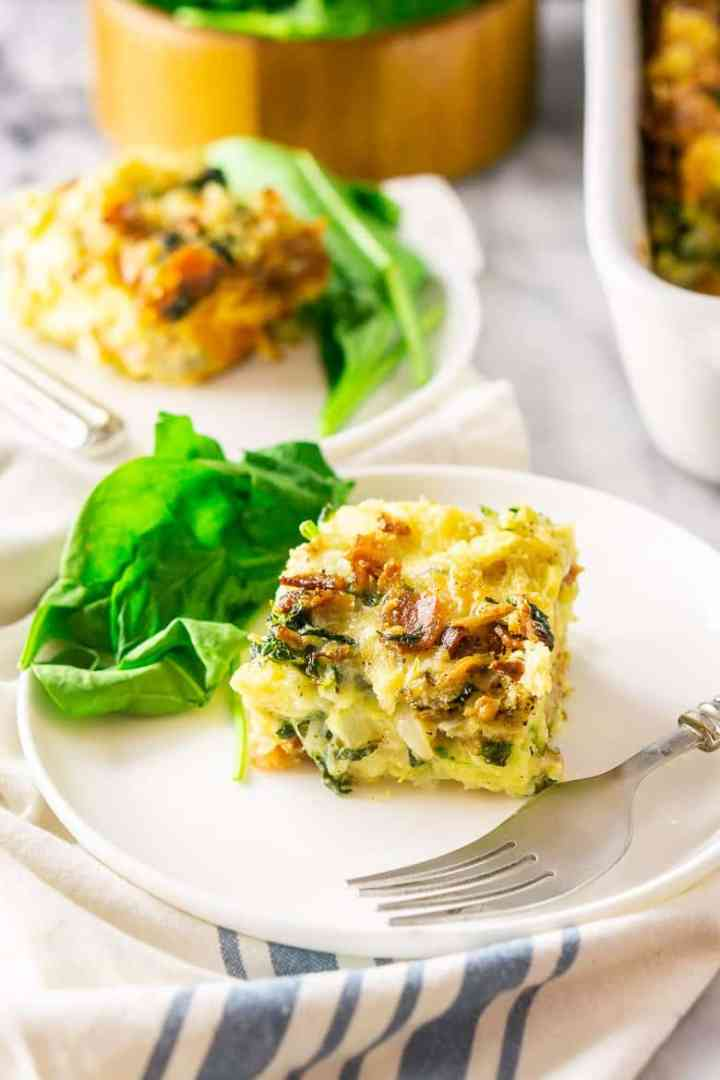 A closeup of a piece of bacon, Gruyere and spinach strata on a white plate.