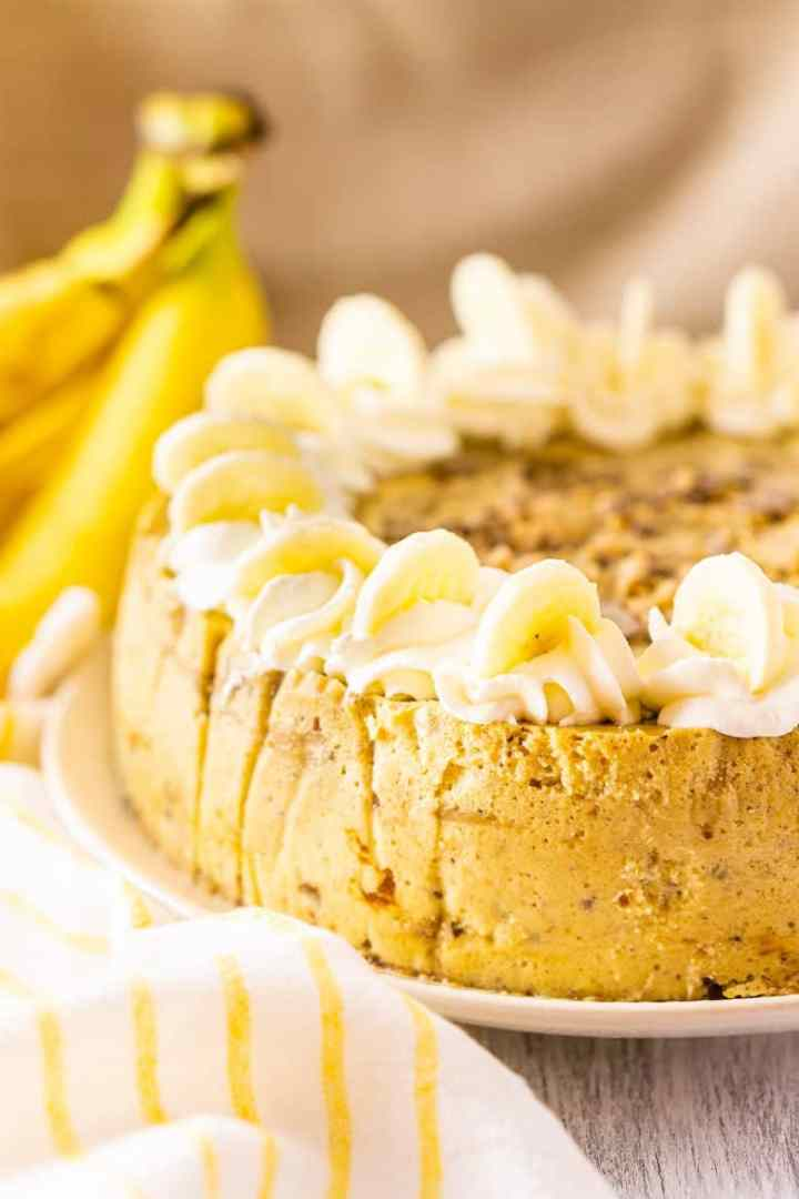 The toffee-bananas foster cheesecake with bananas and a yellow and white napkin.