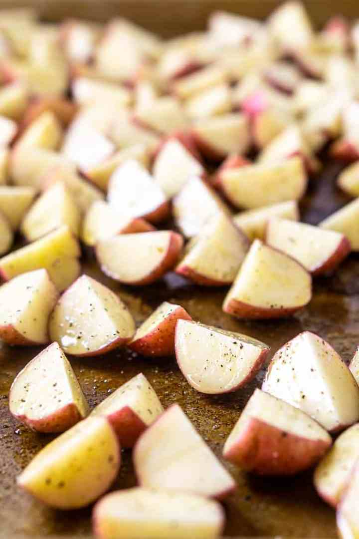 A sheet pan of uncooked potatoes cut into chunks for the herbed roasted potato salad.
