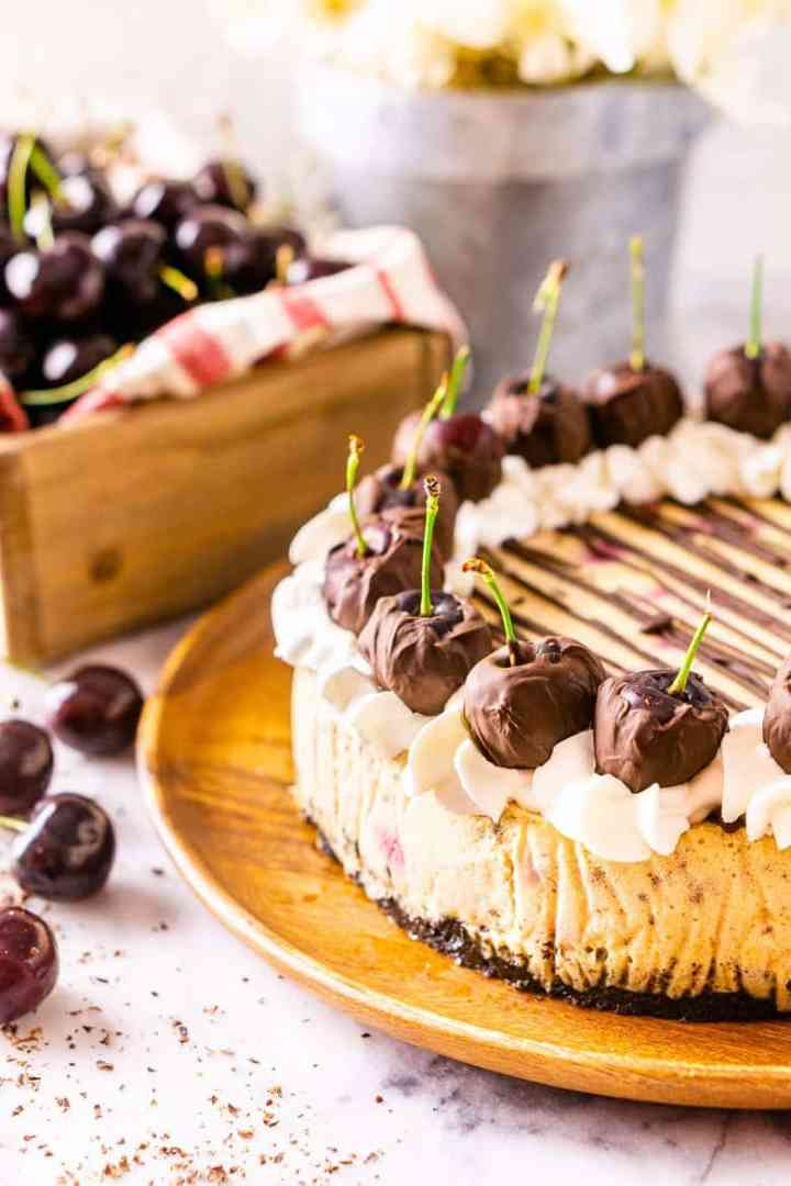 An aerial view of the whole chocolate-covered cherry cheesecake with fresh cherries.