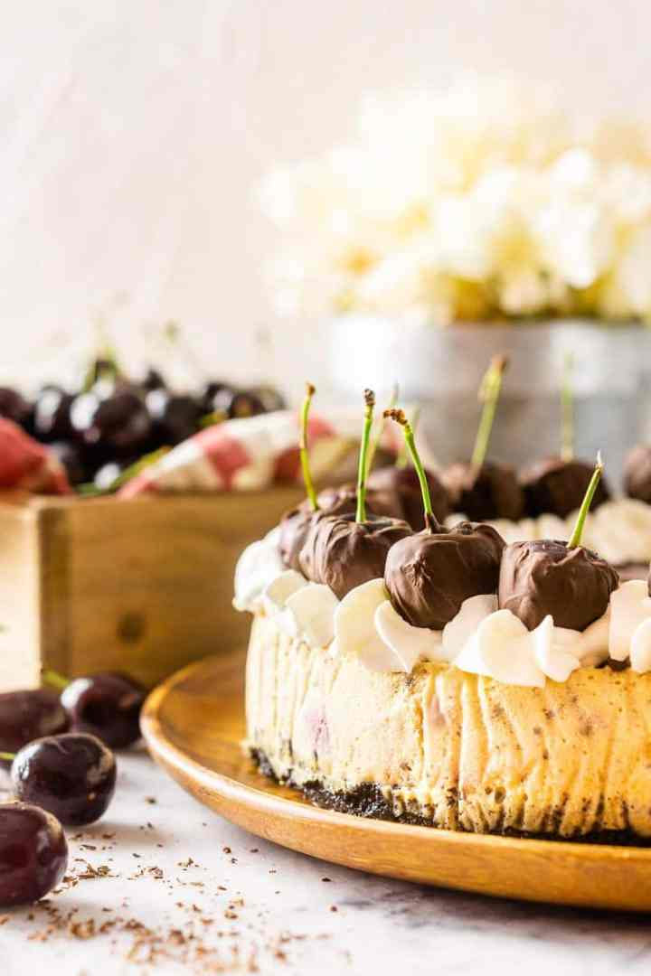 An uncut chocolate-covered cherry cheesecake on a wooden plate with fresh cherries.