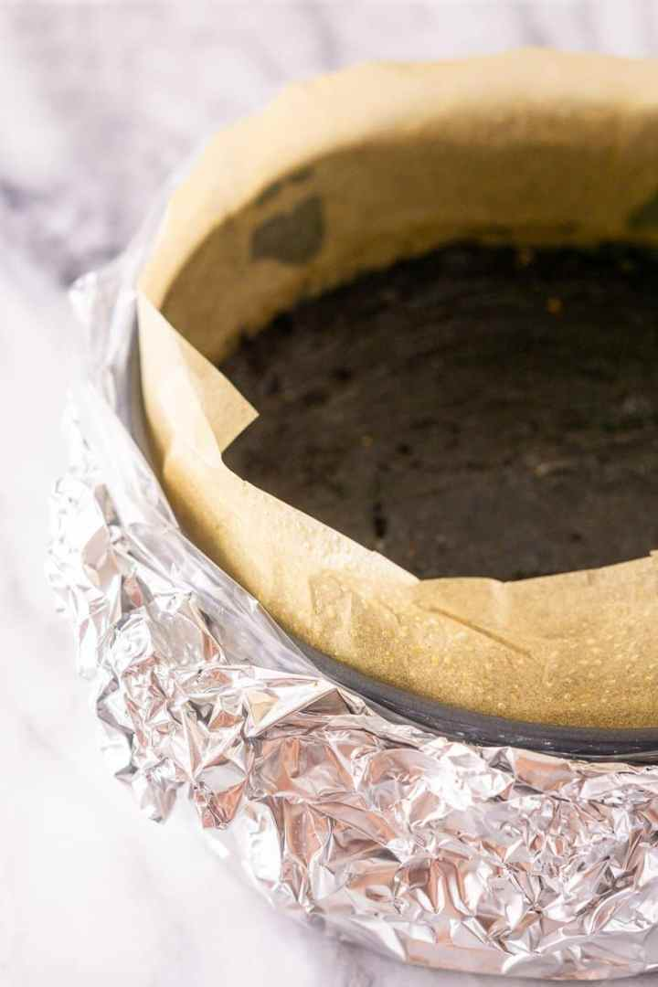 A springform pan wrapped in an oven bag with foil.