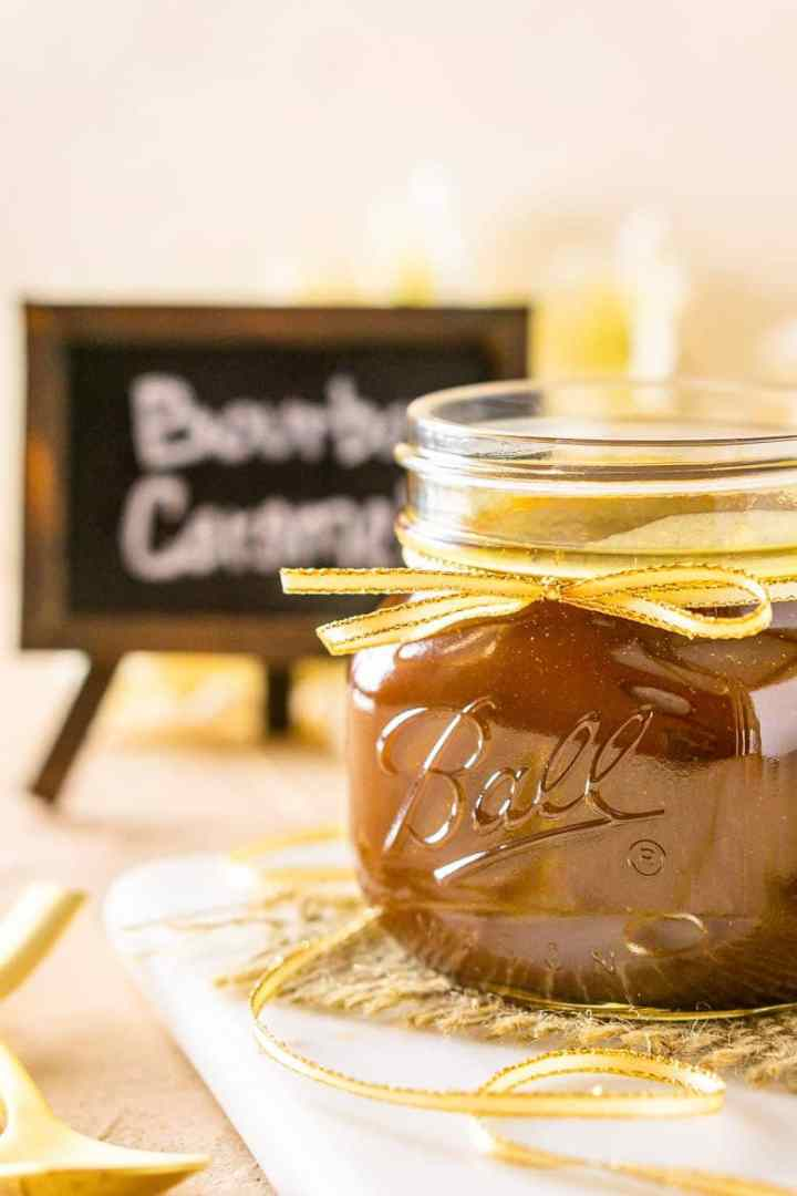 A jar of bourbon caramel sauce turned to the side on a marble tray.