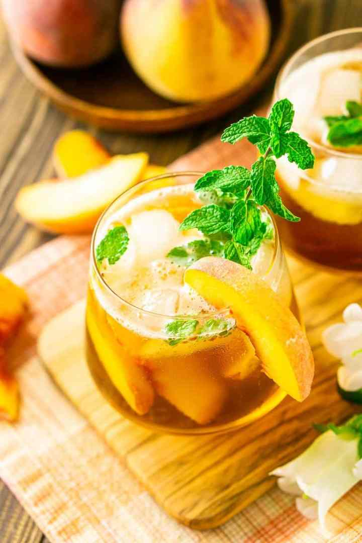 Looking down at a peach-maple bourbon smash from the side with peach slices and whole peaches.