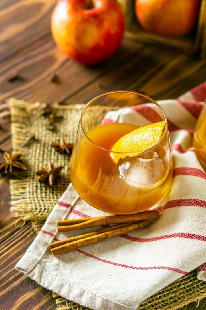 An apple cider old fashioned on burlap with spices.