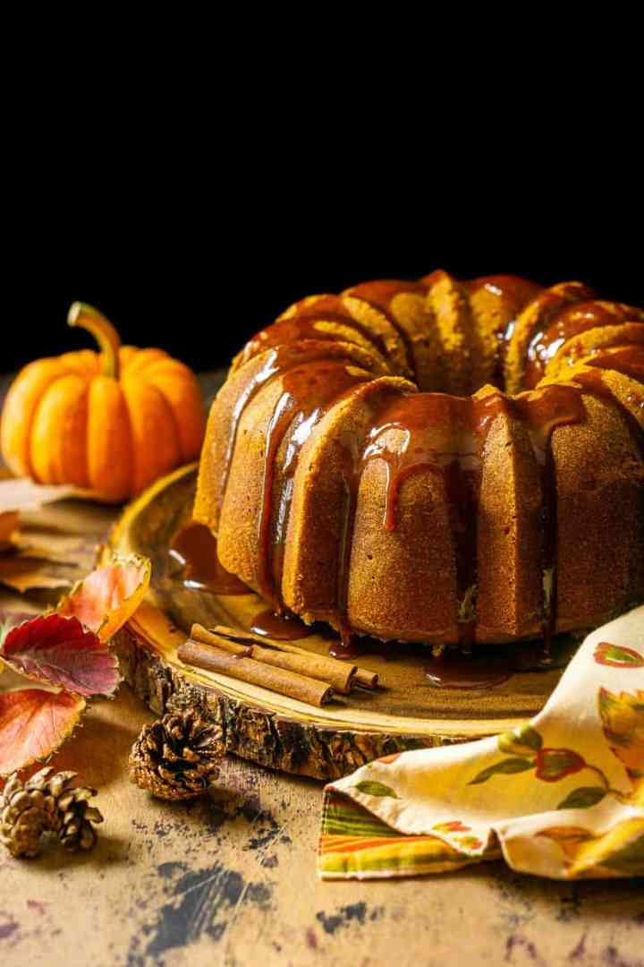 Looking slightly down on the buttermilk-pumpkin pound cake with fall foliage around it.