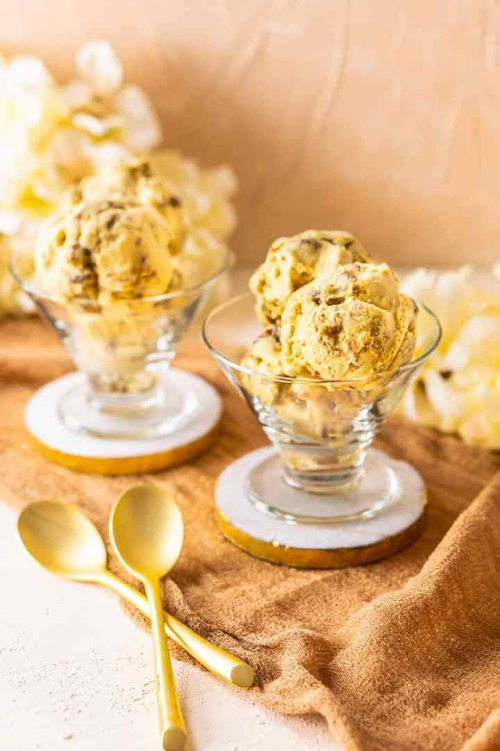 Two dishes of butterscotch ice cream with candied pecans and flowers in the background.