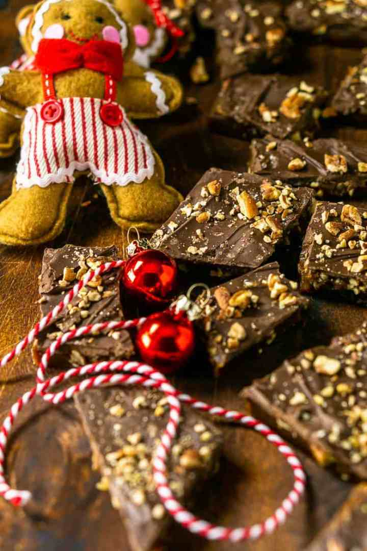 Gingerbread toffee on a wooden board with red Christmas ornaments.