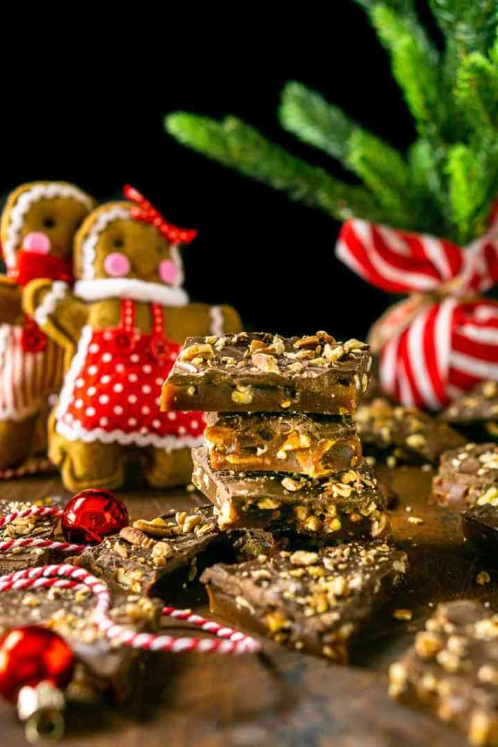 A stack of gingerbread toffee with gingerbread people ornaments and a small Christmas tree in the background.